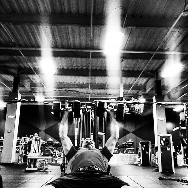 Black and white photo of a man performing a set of incline dumbbell press with the weights extended above his head.