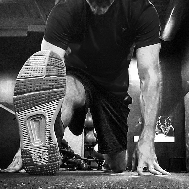 Black and white image of a man's right leg extended in a split stretch.