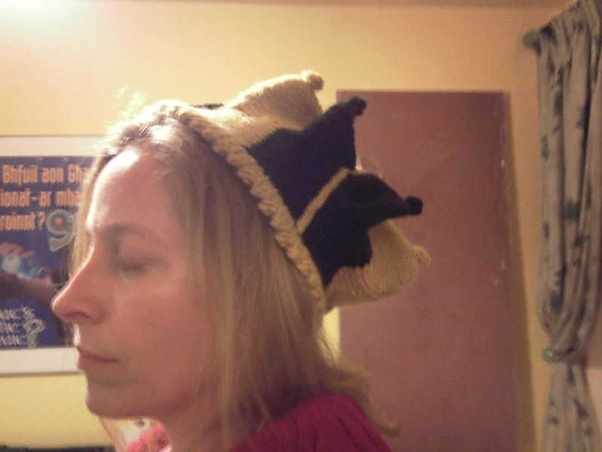 Author wearing a crown-like hat knitted in alternating pointy segments of yellow and black, topped with bobbles.