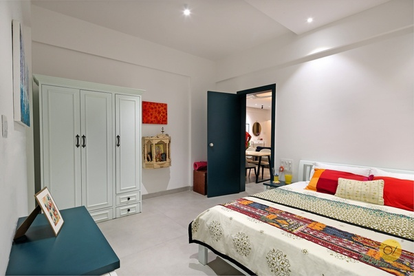 Apartment bedroom with white cupboard, wood temple, cobalt blue door & a custom bed