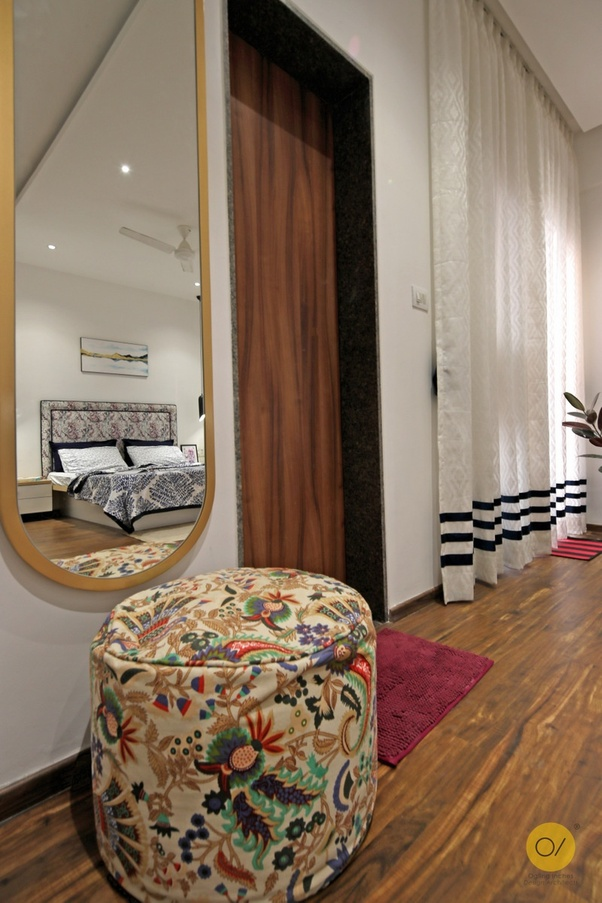 Designer wall mirror & multi color stool, sheer curtains & wood door in the bedroom