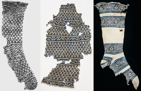Egyptian sock fragments, c. 1000–1400CE, with colourwork geometric designs in black, white and blue cotton.
