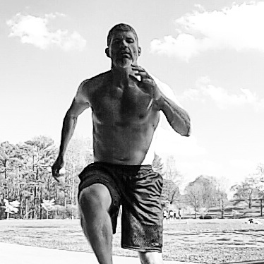 Black and white image of Brandon Sprinting towards the camera showing his knee lift and arm motion.