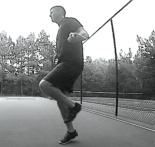 Black and white side view photo of Brandon performing jump rope skips.
