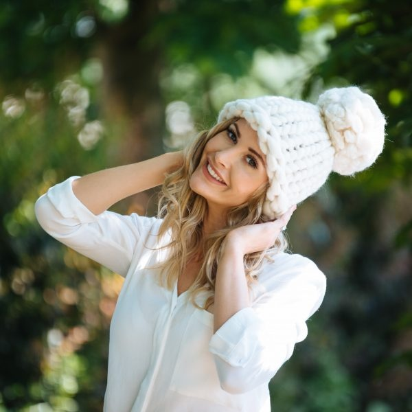 A woman wears a white bobble hat in extreme bulkyweight yarn. The pom-pom is almost as big as her head.