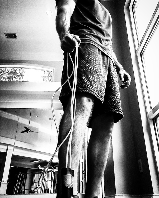 Black and white image of a man clinching a jump rope in his right hand with it dangling by his side.