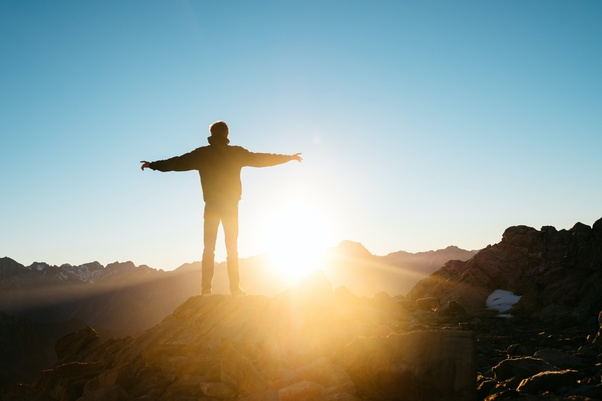Man staring at sunrise with arms open wide.