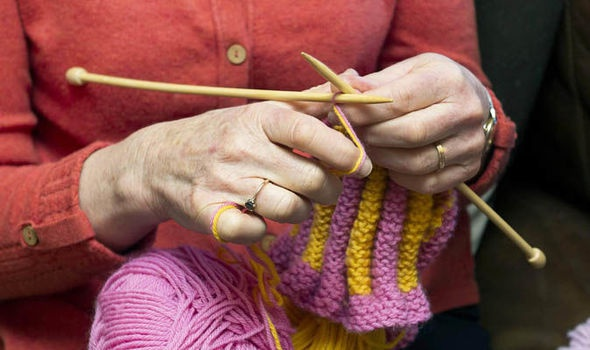 Image of a woman knitting - her hands hide some of the action of knitting.