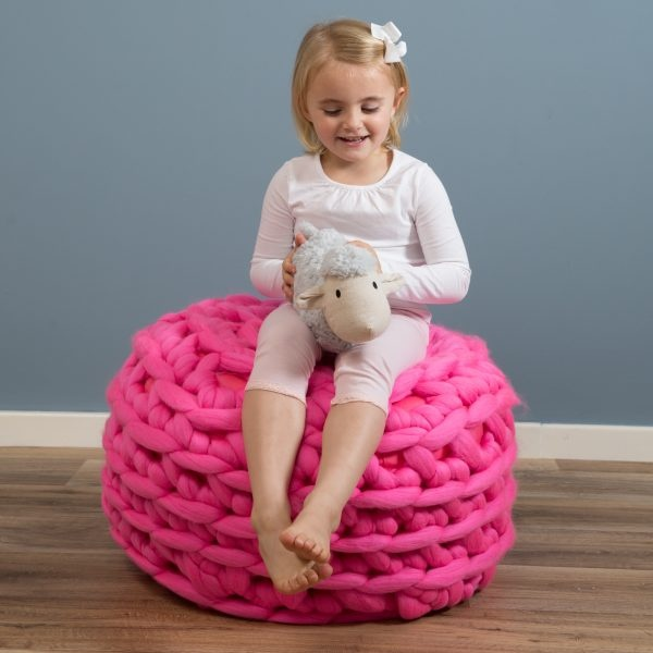 A child sits on a pink footstool crocheted in extreme bulkyweight yarn. The footstool is worked as a sphere, with approximately 8 rounds of (UK) double-crochet stitches.