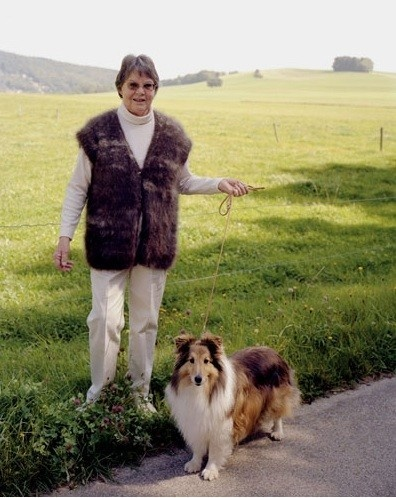 A woman in a dark-brown dog-hair gilet, with rough collie who is too light-coloured to be the dog-hair donor.