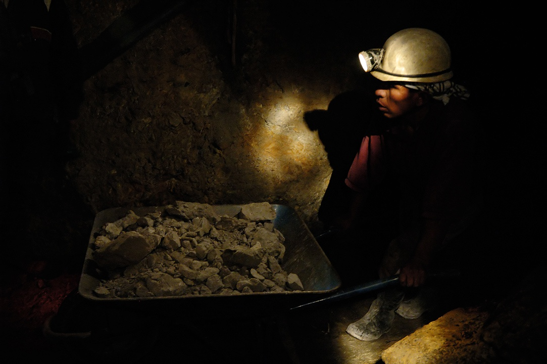 un minero dentro de una mina con una carreta