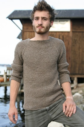A man wearing a wide-necked, textured sweater with raglan sleeves
