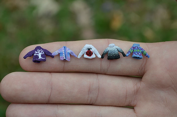A woman's hand, with 5 perfectly formed colourwork sweaters laid side by ide along her index finger.