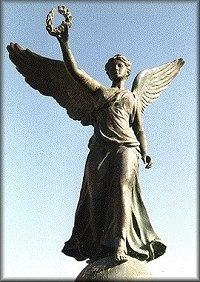She was represented in statues and paintings as a woman with wings, dressed  in billowing robes, with a wreath and/or a palm branch in her outstretched  hand.