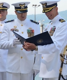 A Coast Guard warrant officer (left) and officer (right) wearing Full Dress  Whites. The ... 0e9501f1e