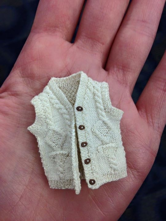 A tiny Aran vest, resting in the centre of a woman's palm.