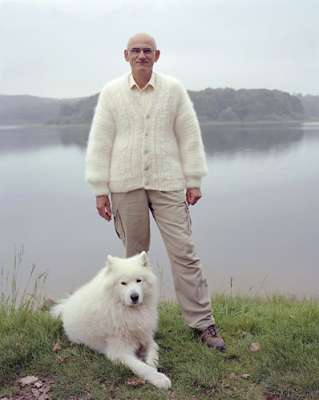 A man in a bright white Aran-style cabled cardigan, with a beautiful white husky.