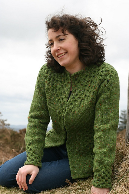 Carol Feller, wearing her Killybegs cardigan, in Studio Donegal Aran Tweed in shade Green (4824). The cardigan is has a round collar and opens from throat down, and features a delicate honeycomb cable pattern at the cuffs, waist, and yoke.