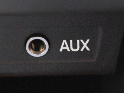 What is an auxiliary audio input jack and what does it do