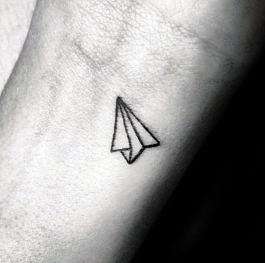 paper airplane tattoo on finger