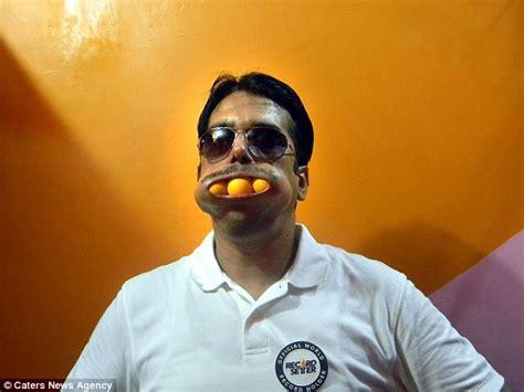 Homem com várias bolas de sinuca dentro da boca