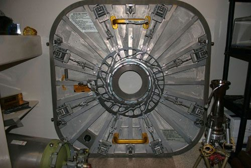 This appears to be an airlock hatch for space (see space suits on left and right). The round stuff in the middle would be the central lock assembly. & What is the round stuff in the middle of the door for and how is it ...