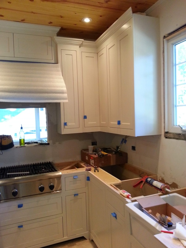 Why don't most kitchen cabinets touch the ceiling? - Quora