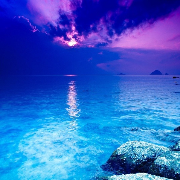 The Crystal Blue Water That Grows Dark And Merges With Purple Sky Sun Glowing Bright White Landing A Streak Of Across