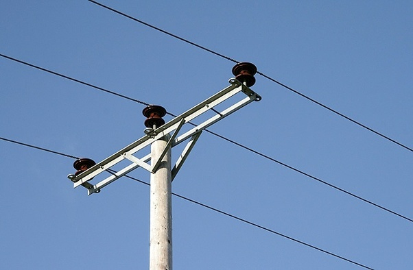 Why don't we get shock when we touch an electric pole while