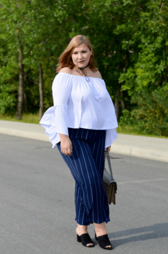 deee44417d7 Off-shoulder tops can be matched with navy pants to create a sophisticated  look. This high low flutted sleeves off-shoulder top is from Ashley Stewart.