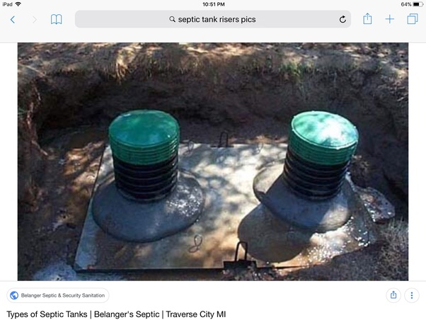 A septic tank lid made of concrete is cracked in half and ...