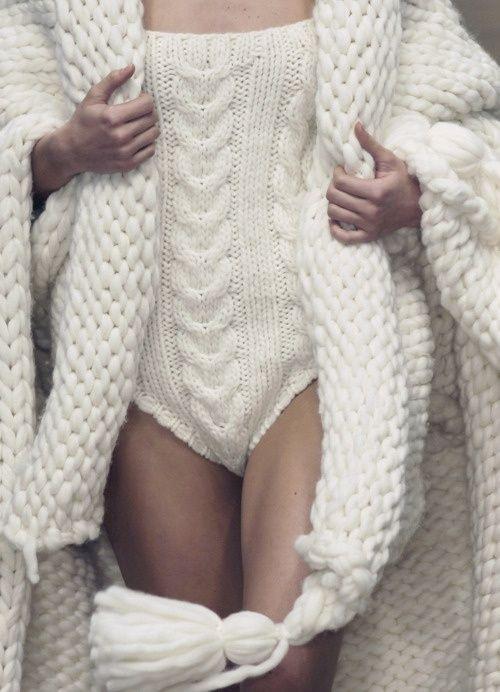 Model wearing an Aran bodysuit and a tasseled stole in a super-bulky weight yarn