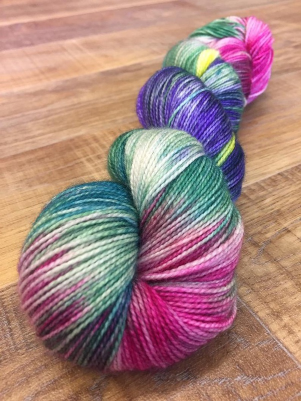 Skein of hand-painted yarn in shades  of pink. green, purple and yellow.