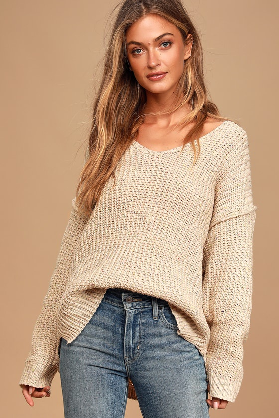 A woman in a v-necked ribbed sloppy joe sweater with drop sleeves falling  roughly to the elbow,