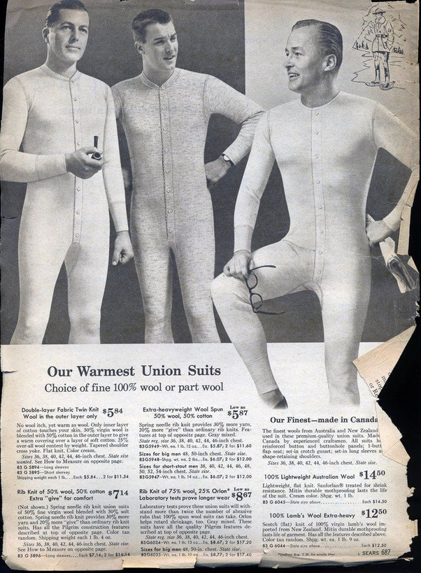 A 1920s newspaper advertisement for men's commercial woollen underwear, featuring 3 men in full-body button-fronted Union suits in fine 100% wool or part wool, one smoking a pipe, one holding a newspaper and reading glasses, and all 3 looking remarkably happy to be standing around together in their underwear as if that was a completely normal thing to do in the 1920s.