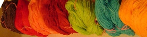 7 hanks of yarn dyed in solid maroon, red, salmon, burgundy, lime, turquoise and orange.