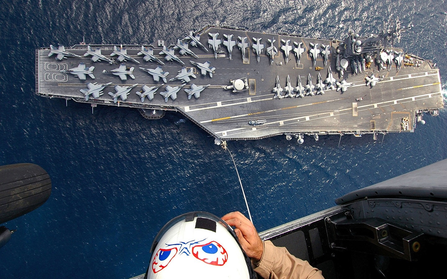 Why don't US aircraft carriers land planes straight and launch at an